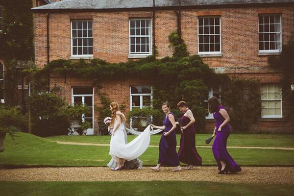 Bridesmaids holding up brides' dresses