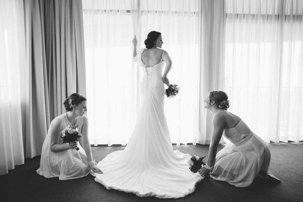 Bride having dress adjusted