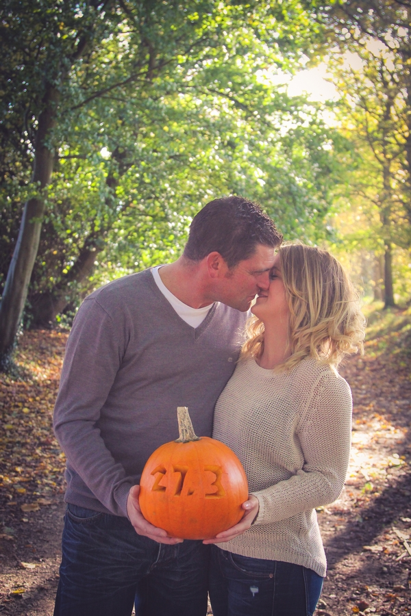Couple holding pumpkin about to kiss