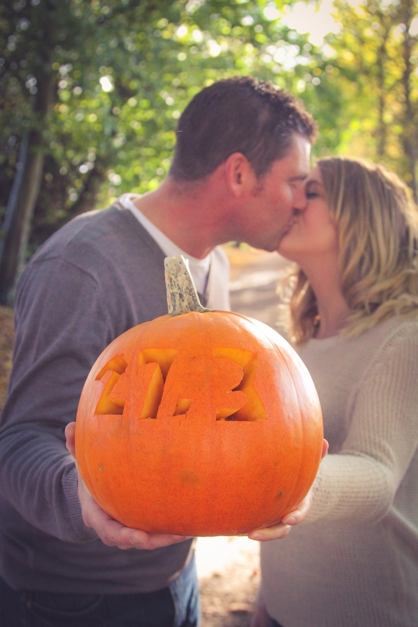 Couple holding pumpkin and kissing