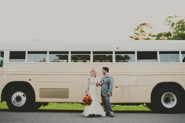 Bride and groom in front of vintage bus