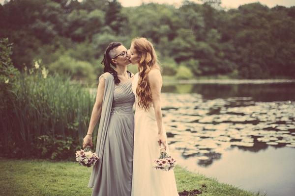 Brides kissing by lake
