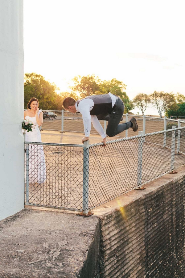 Groom jumping fence