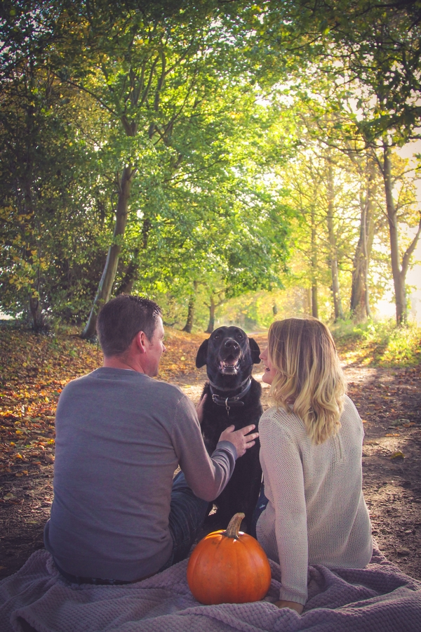 Couple sitting with dog in woods at Quakers Walk, Devizes