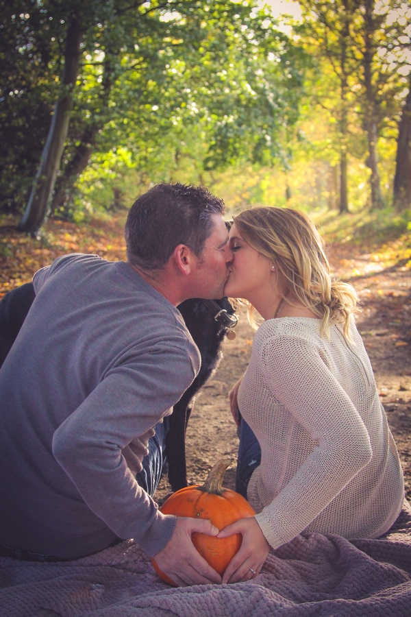 Couple sitting and kissing in woods at Quakers Walk, Devizes
