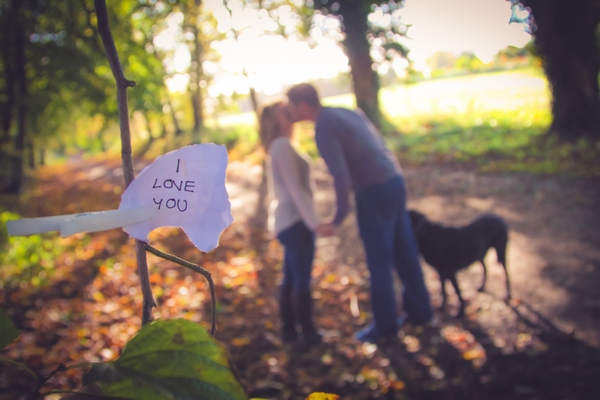 Couple kissing behind paper note saying 'I love you'