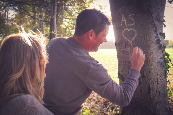 Man writing love note on tree