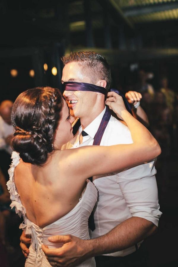 Bride tying tie over groom's eyes