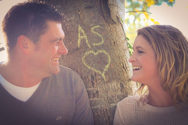 Couple standing next to love note on tree