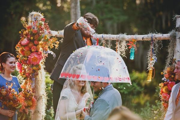 Bride and groom under umbrella in wedding ceremony