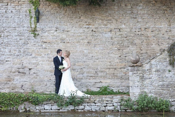Bride and groom standing next to stone wall - Picture by Emma Russell Photography