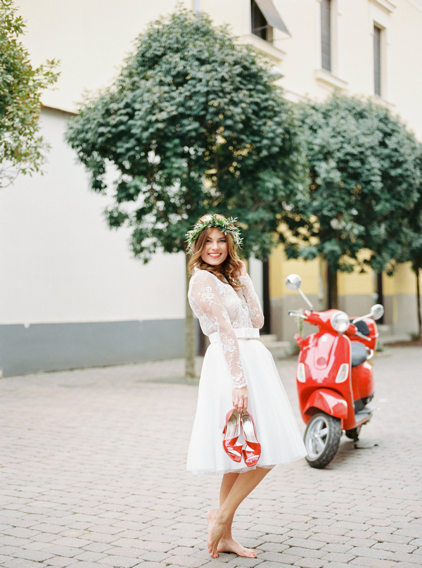 Bride holding red shoes
