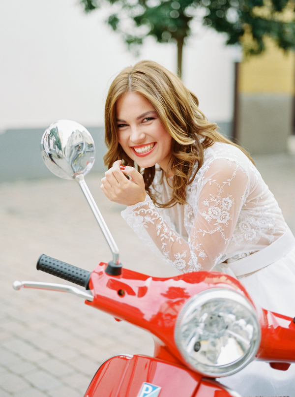 Bride leaning on red Vespa