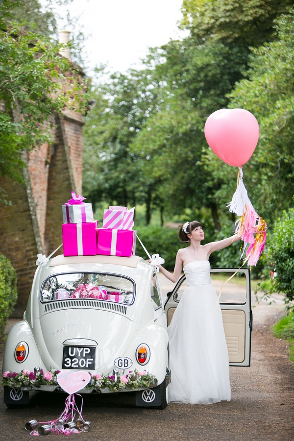 Bride holding pink balloon next to VW Beetle