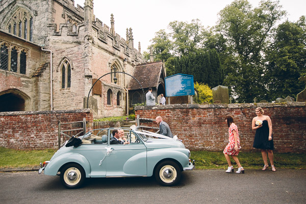 Bride arriving at church in blue Morris Minor