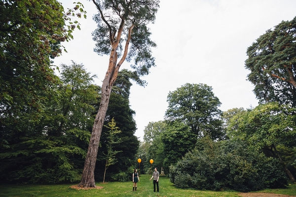 Couple holding orange balloons at Westonbirt Arboretum