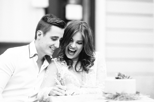 Bride and groom sitting at table writing
