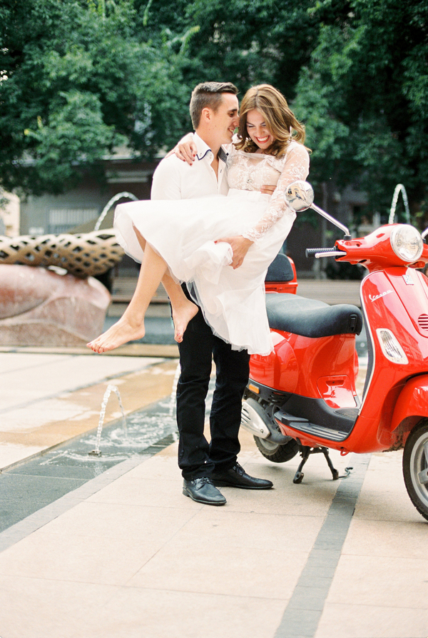Groom holding bride next to red Vespa