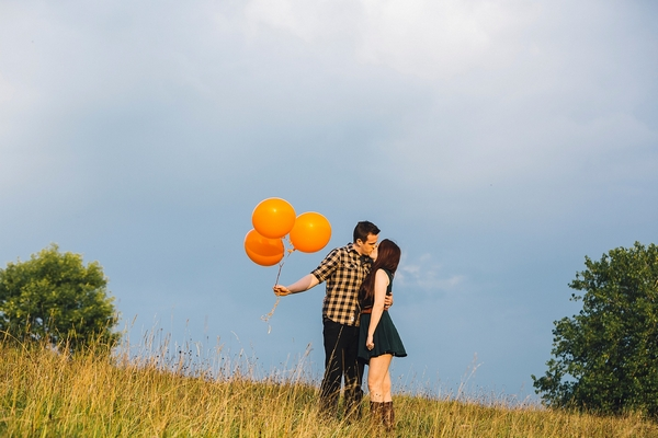 Couple kissing holding orange balloons