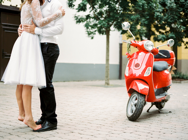 Couple next to red Vespa