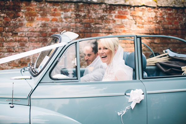 Bride and groom in blue Morris Minor wedding car
