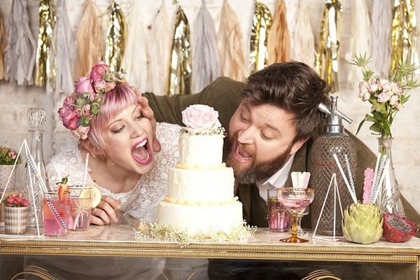 Bride and groom pretending to eat wedding cake