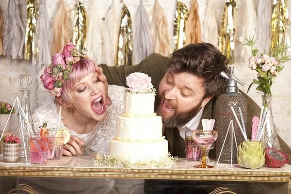 Bride and groom pretending to eat wedding cake