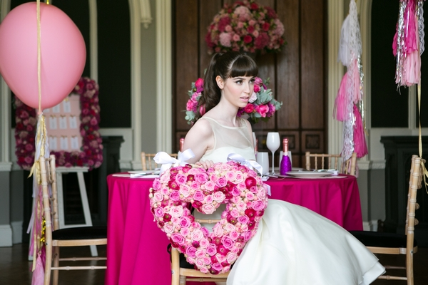 Bride sitting on chair with pink floral heart