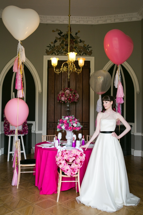 Bride standing next to table with pink styling