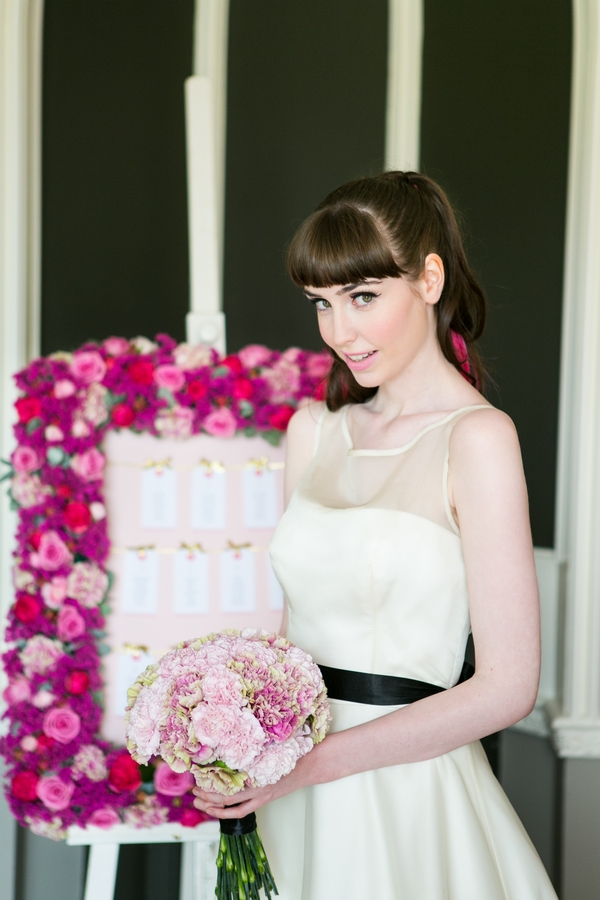 Bride standing next to pink floral table plan