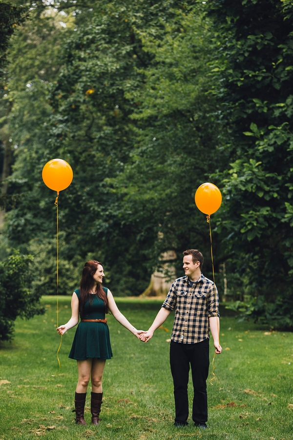 Couple holding orange balloons