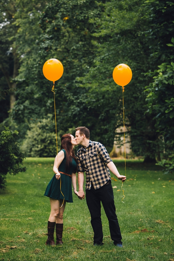 Couple holding orange balloons kissing