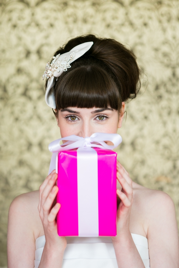 Bride holding pink present in front of face