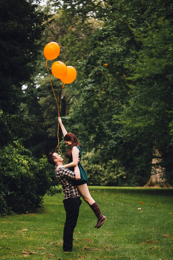 Man lifting up woman holding orange balloons