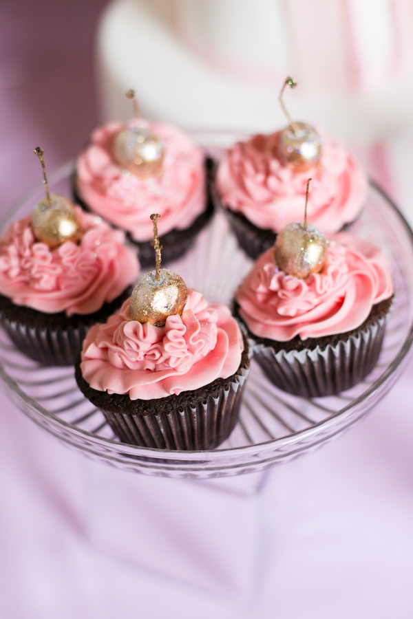 Pink cupcakes with gold cherries