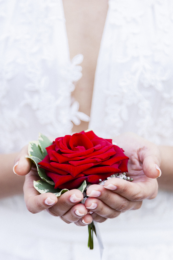 Red rose in bride's hands