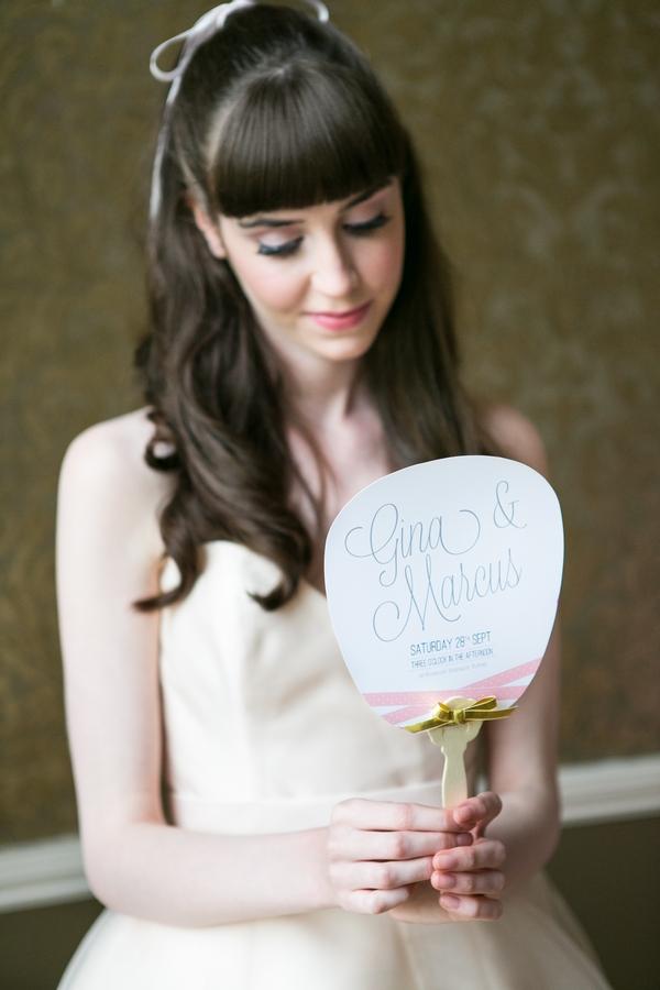 Bride holding paddle wedding invitation