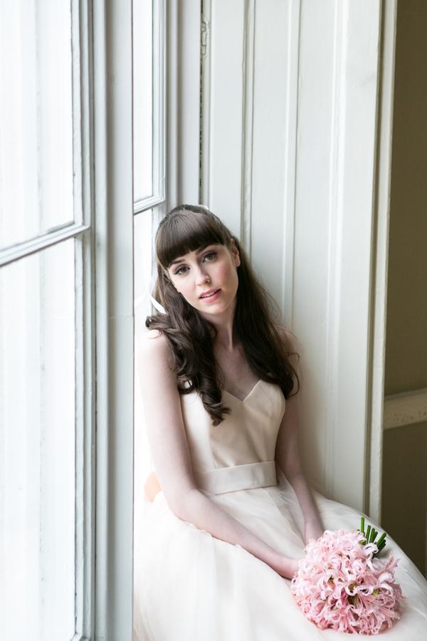 Bride sitting on window ledge