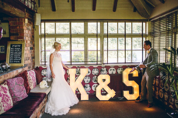 Bride and groom in room with large illuminated letters