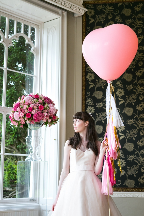 Bride holding pink heart balloon