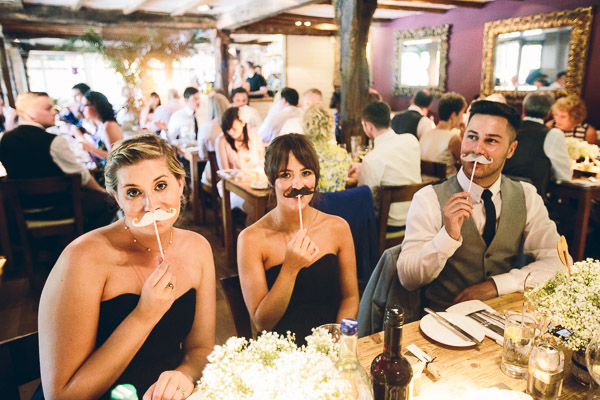 Wedding guests putting moustaches to their faces