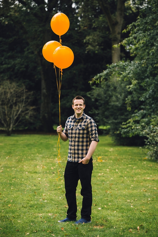 Man holding orange balloons