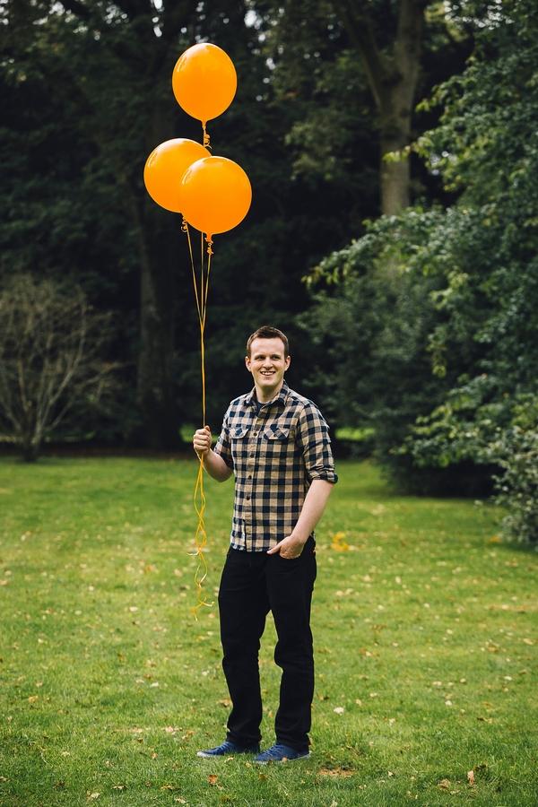 Man holding orange balloons