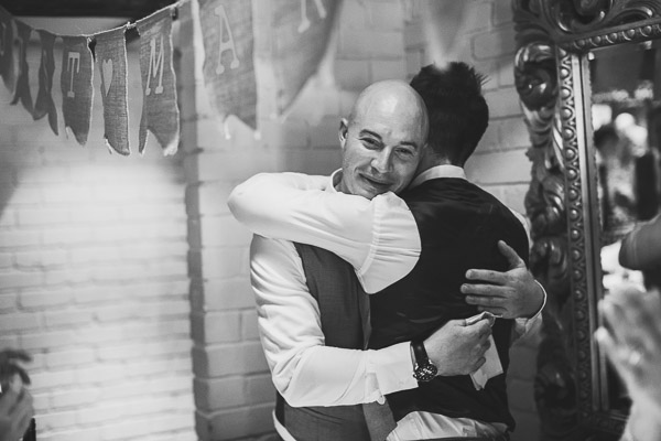 Groom and best man hug