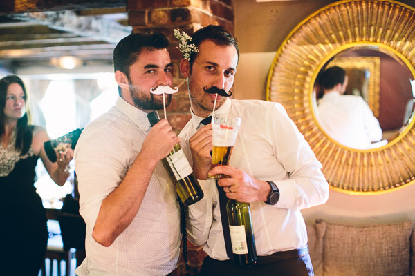 Wedding guests with moustaches on sticks