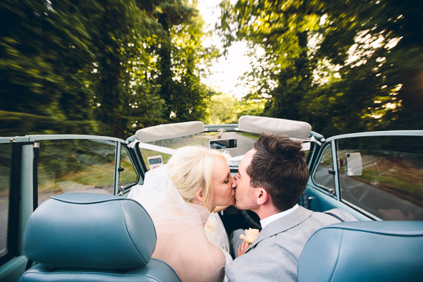 Bride and groom kiss in car