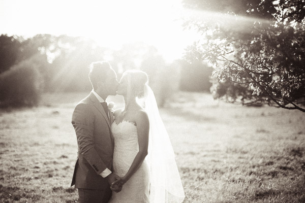 Bride and groom kiss in hazy sunshine