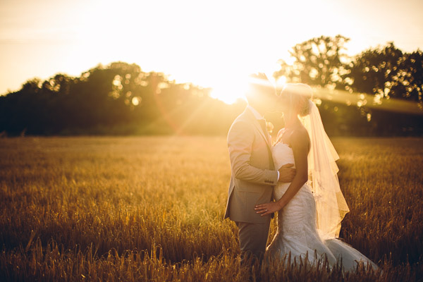 Bride and groom in field in hazy sunshine