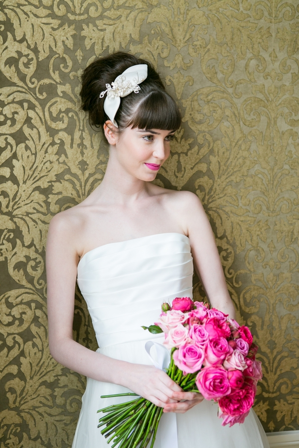 Bride leaning against wall holding pink bouquet