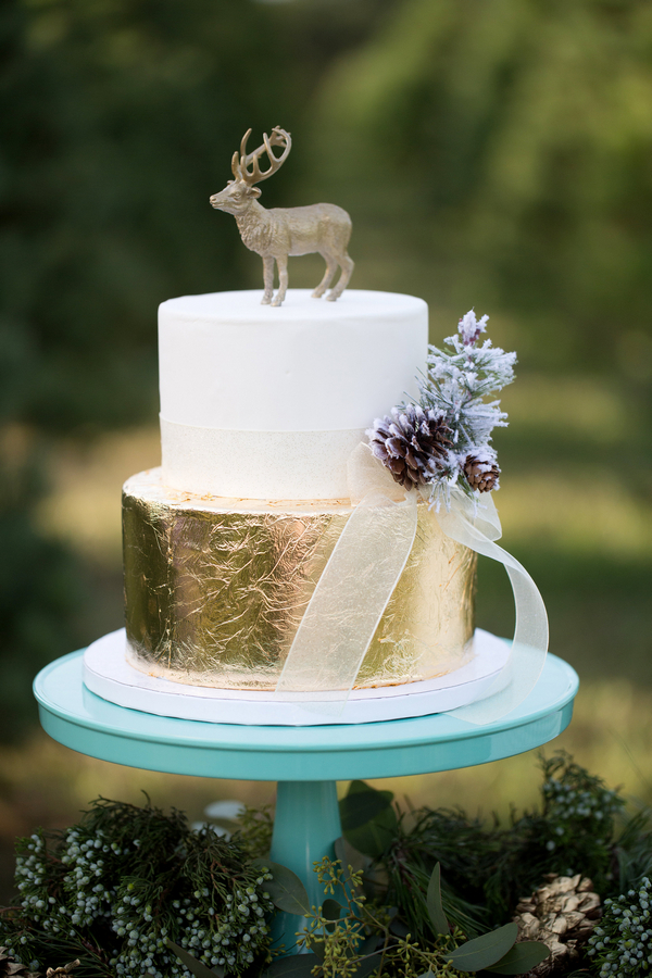 Gold and white wedding cake with reindeer cake topper